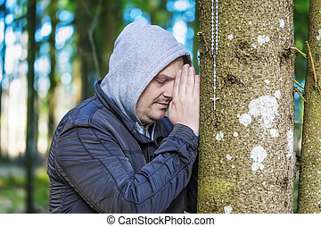 Religious man with a rosary near tree in the park
