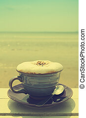 Coffee cup on grunge terrace facing seascape with vintage filter effect