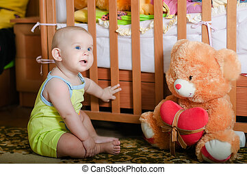 Infant baby playing on the floor at home with teddy bear