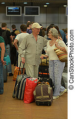 Senior couple at the airport - Senior couple with bags at...