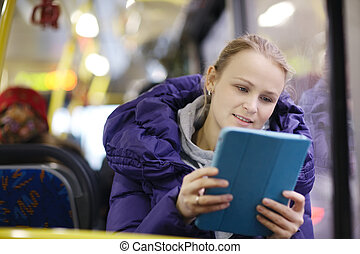 Woman with touchpad in the bus - Young woman in purple...