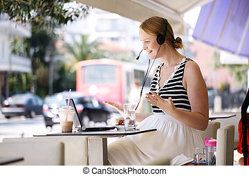 Laughing woman wearing a headset in outdoor cafe - Laughing...