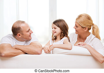 smiling parents and little girl at home - family, child and...