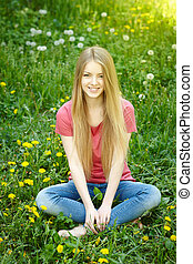 Smiling female sitting on the field of dandelions looking at...