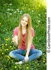 Smiling female sitting on the field of dandelions - Spring...