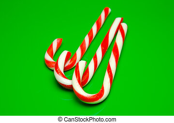 Candy Canes - Christmas candy canes isolated against a green...