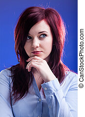 Pensive woman with red hair on a blue background