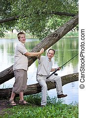 The father with the son on fishing Rejoice to a biting