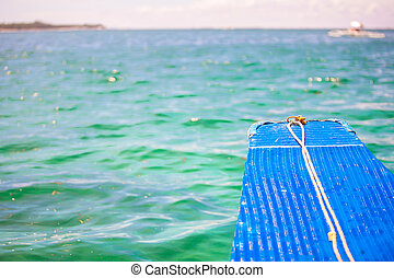 Small blue boat in open sea on desert island