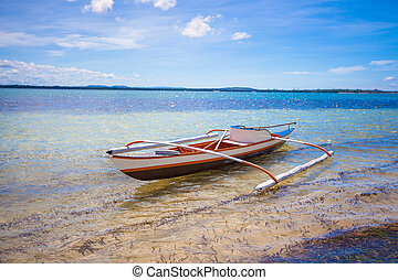 Small fishing boat in turquoise lagoon