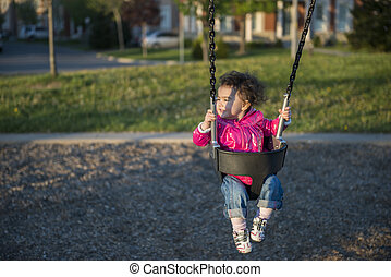 Little girl having fun in Swing at the Park