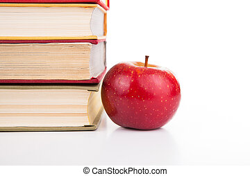 stack of books with red apple