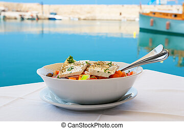 Greek salad. Crete - Greek salad with feta cheese on table....