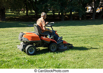 lawnmower - man on tractor mow the grass in the city park