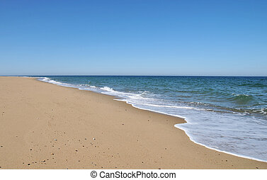 Ocean's Edge - Waves from the receding tide lap the sand at...