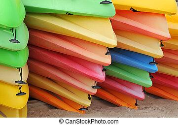 Kayaks - Piles of sherbet colored kayaks put away for the...