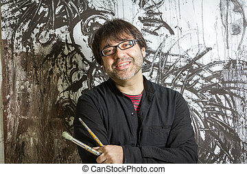 Painter artist posing in front of paint
