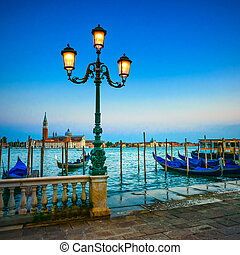 Venice, street lamp and gondolas or gondole on a blue sunset twilight and San Giorgio Maggiore church landmark on background. Italy, Europe.