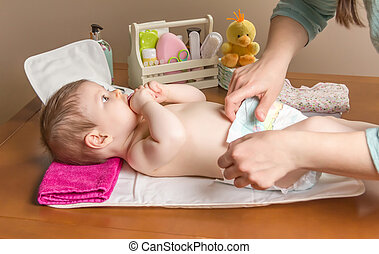 Mother changing diaper of adorable baby with a hygiene set...