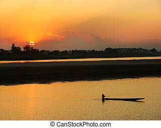 Silhouetted boat on Mekong river at sunset, Vientiane, Laos,...