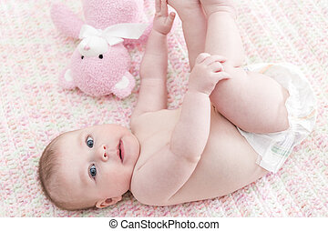Infant baby girl playing on a pink blanket
