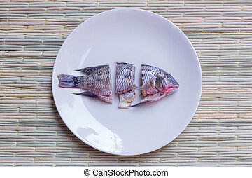 choped fish - small choped fish in round dish, on a...
