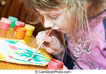 Girl painting in preschool