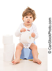 Amazed boy sitting on potty and holding rolls of paper...