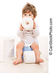 Toddler boy sitting on potty holding rolls paper and looking...