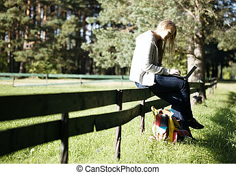Young woman sitting on a rustic fence using her laptop...