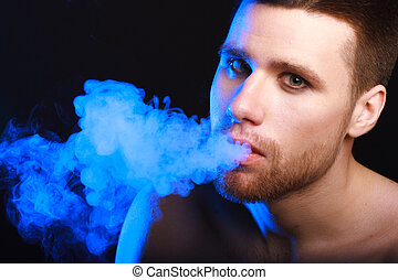 dark and sullen shot of a young man smoking over a black...