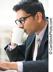 close up of young indian business man enjoying coffe during...