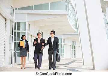 asian business team walking in office background