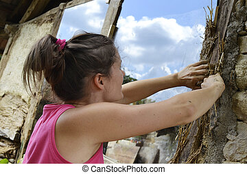 Cob work - Young female plastering a old stone building with...