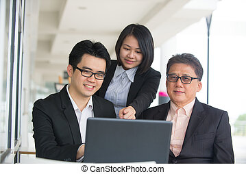 Group of asian business people gathered together at a table...