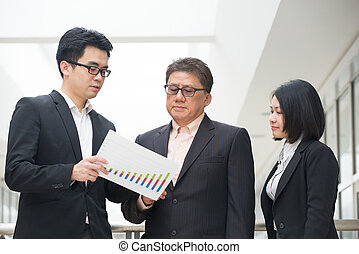 asian business team reporting to senior ceo with office backgrou