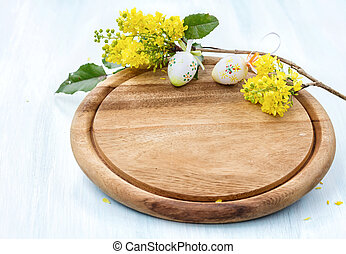 Cutting board with a blossoming branch and easter eggs.