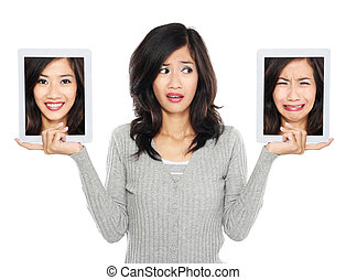 Woman with two tablet computer screen. one with smiling face...