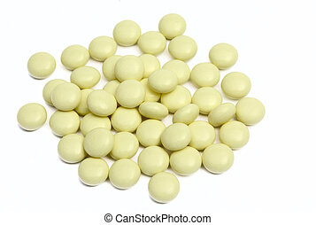 yellow tablets with a jar - Heap of yellow tablets on a...