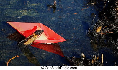 Paper boat in a puddle of oil