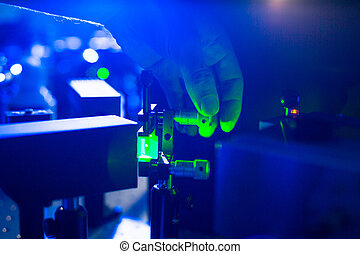 Quantum optics - hand of a researcher adjusting a laser beam...
