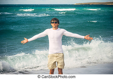 Man Traveler with raised hands outdoor Sea on background Freedom Lifestyle concept