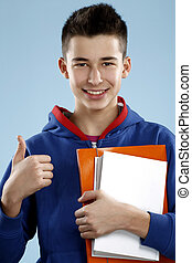 young smiling male student teenager holding a book on blue