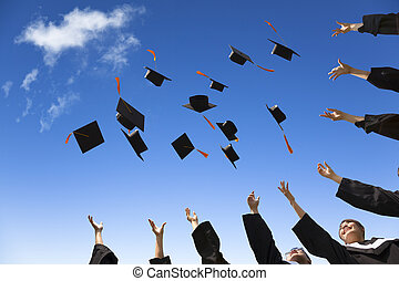 Students throwing graduation hats in the air celebrating