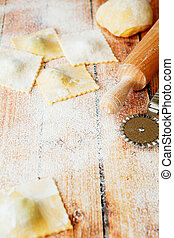ravioli stuffed with cheese and rolling pin on the table,...