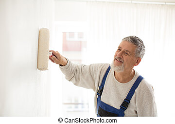 Senior man painting a wall in his home, smiling, enjoying...