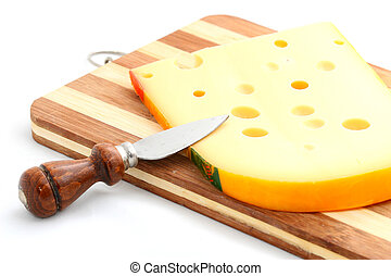 cheese cut in slices on a wooden plate