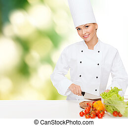 smiling female chef chopping vagetables - cooking and food...