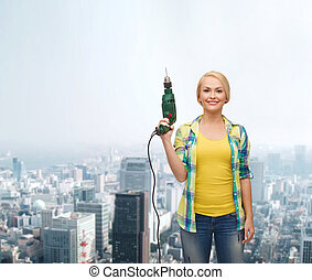 smiling woman with drill machine - repair, construction and...