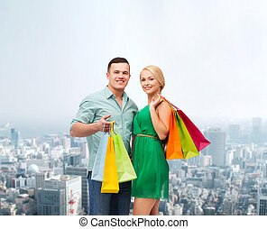 smiling couple with shopping bags - happiness, shopping and...